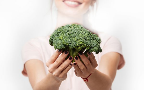 Close up of a smiling woman showing broccoli isolated over white