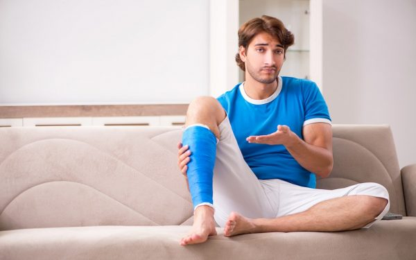 Leg injured young man on the sofa