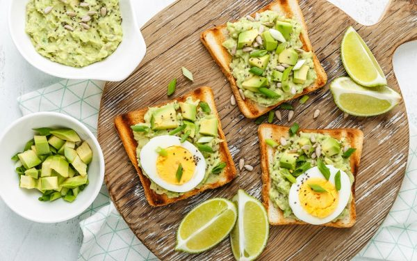 avocado toasts top view, healthy snack of grilled bread with guacamole slices avocado, boiled eggs, chia seeds and green onions