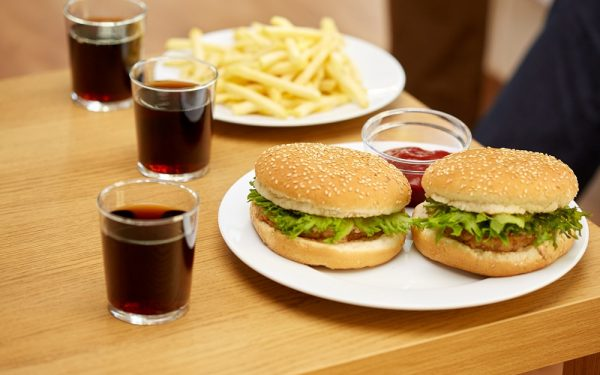 close up of fast food and drinks on table at home